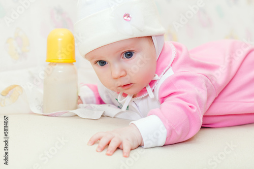 Little baby with bottle of milk