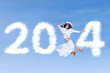 Woman jumping with new year 2014 on the sky