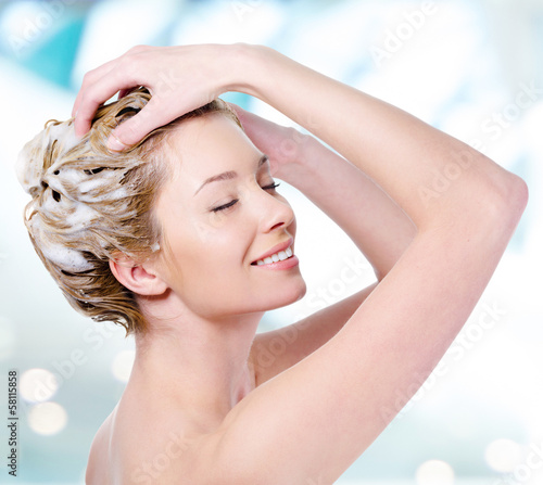Smiling woman soaping her hair