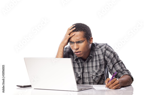 unhappy young black man writes data from his laptop