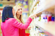 beautiful women choose personal care product in supermarket