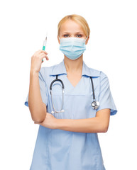 female doctor or nurse in mask holding syringe