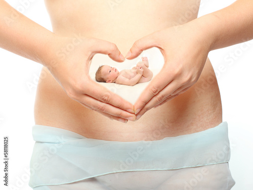 A woman's hands forming a heart symbol on belly with baby.