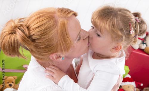 Mutter und Tochter geben sich einen Kuss