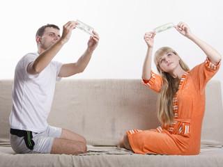 Молодые парень и девушка определяют фальшивые ли банкноты