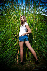Sexy woman in denim shorts posing against high grass