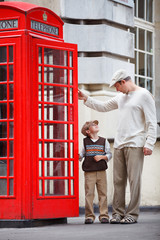 Happy father and son outdoors in city by red phone booth