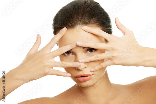 Attractive female with hands on her face. Spread fingers.