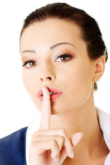 Attractive business woman with finger on lips.