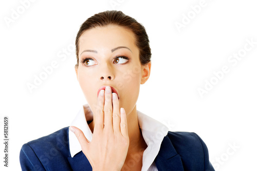 Attractive businesswoman covers her mouth.