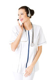Young attractive nurde with stethoscope and headphones and micro