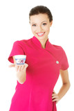 Beautiful attractive beautician holding a cream.