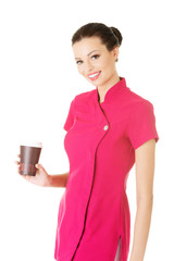 Attractive woman in pink uniform holding a cup.