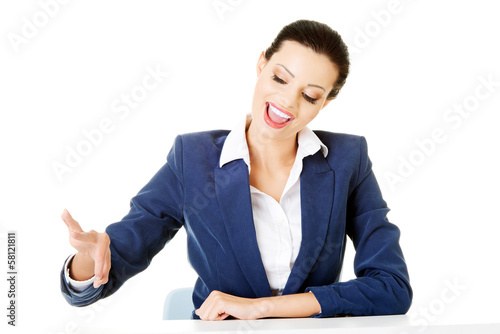 Attractive woman holding copy spacein the air.