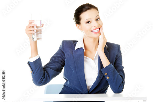 Attractive business woman sitting holding a glass.