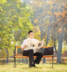 Businessman seated on a bench reading a newspaper in a park