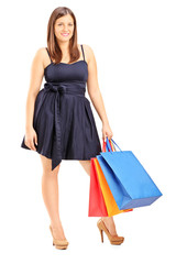 Young female wearing dress and holding shopping bags