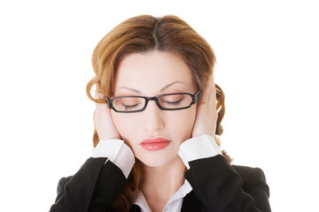 Business woman covering her ears.