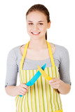 Attractive woman in kitchen apron with knives.