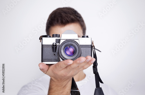 Photographer holding a camera against gray background