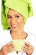 Attractive woman wrapped in towel with turban on head, holding a