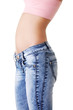 Woman's belly and jeans. Side view.