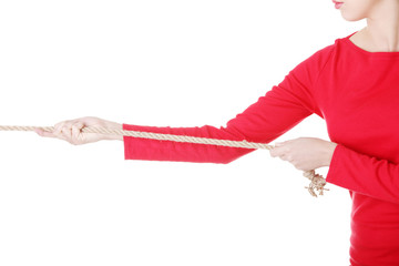 Attractive young woman puuling a rope.