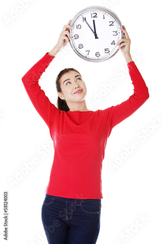 Attractive young woman holding a clock.