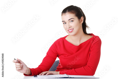 Happy casual woman sitting by a table.