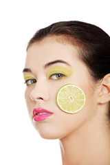 Beautiful woman's face with lime on cheek.