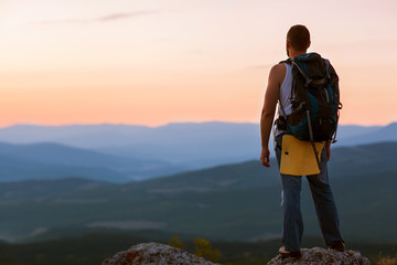 guy in the mountains at sunset. the concept of freedom