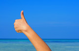 Hand with thumb up on blue sky and sea background