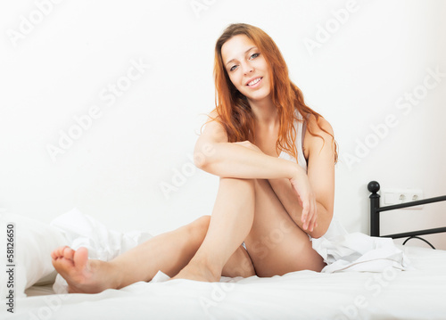 Beautiful red-haired sensual girl in shirt awaking on white shee