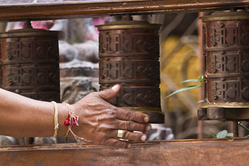 Brahman moving prayer wheel in buddhist temple