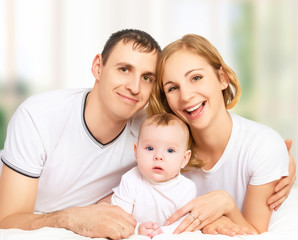 happy family of father, mother and small  baby girl daughter in