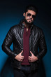 young man with long beard is holding his leather jacket