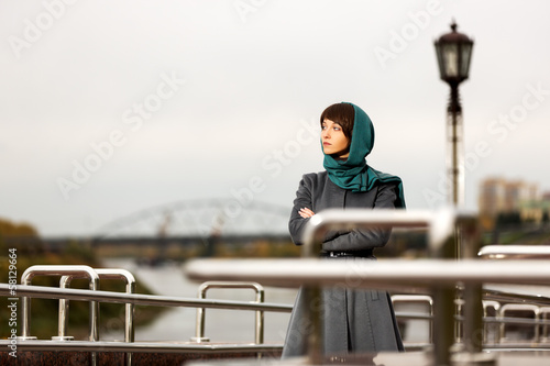Sad young woman in grey classic coat