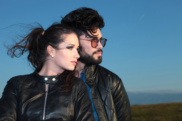 side view of a young couple against blue sky