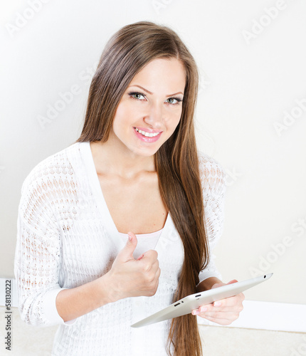 Woman at home websurfing on internet with tablet
