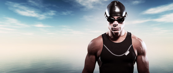 Swimmer triathlon muscled man with cap and glasses outdoor at a