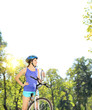 Young female biker posing on a mountain bike on sunny day