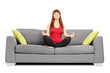 Young female meditating seated on a sofa