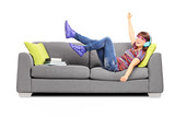 Young excited female listening music seated on a sofa