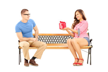 Young female giving a gift box to her boyfriend, on a bench