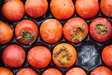 persimmons in a fruit container - kaki
