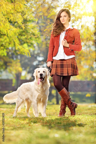 Smiling young woman with her dog in a park