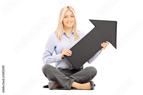 Young blond woman seated on a floor holding a big black arrow