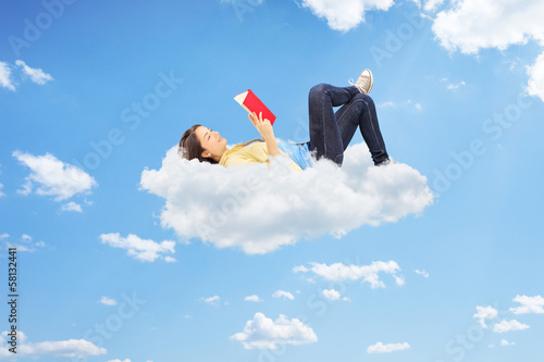 Relaxed female reading a novel and lying on clouds