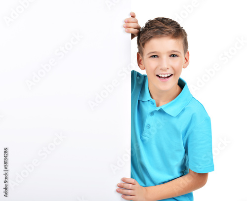 smiling  boy looks out from white banner