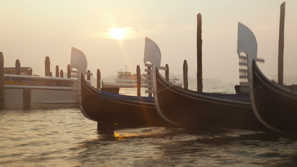 Venetian gondolas tied near the pier at sunrise